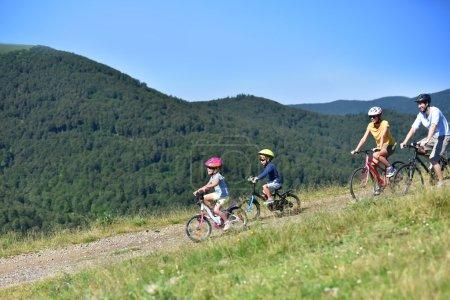 Family of four riding bikes