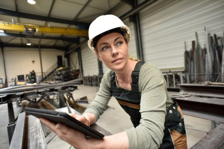 Photo for Metalworker woman in factory using tablet - Royalty Free Image