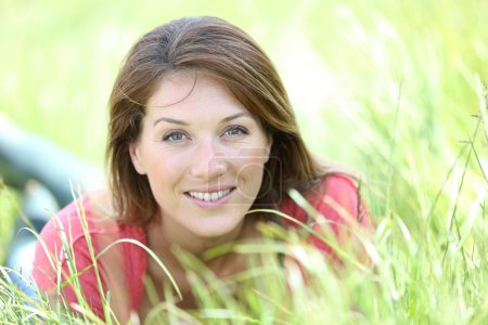 Smiling woman laying in country field