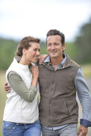 Photo pour Couple joyeux de 40 ans marchant dans la campagne - image libre de droit