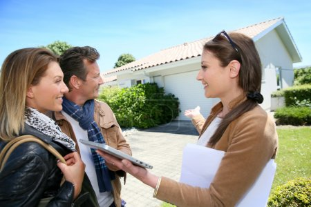 Real-estate agent presenting house to couple