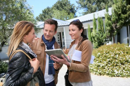 Real-estate agent showing house to clients