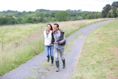 Couple of farmers running in countryside