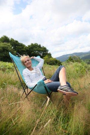 Photo pour Femme âgée se détendre dans la chaise à la campagne - image libre de droit