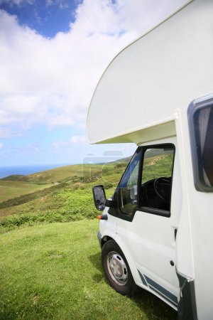 Camper parked on hill by sea