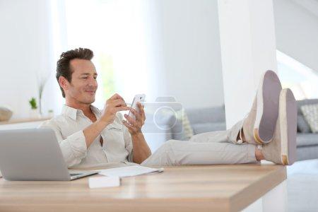 Photo pour Homme détendu travaillant à la maison et utilisant un smartphone - image libre de droit