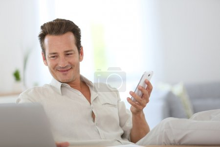 Photo for Relaxed man working from home and using smartphone - Royalty Free Image