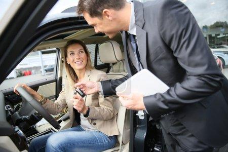 Photo pour Concessionnaire automobile donne la clé au nouveau propriétaire de voiture - image libre de droit