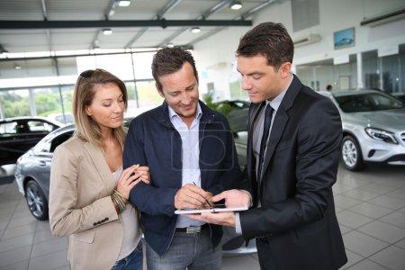 Photo pour Couple de signer l'ordre d'achat de voiture sur tablette numérique - image libre de droit