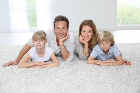 Photo for Happy family of four laying on carpet at home - Royalty Free Image