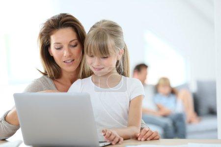 Photo pour Mère et fille à l'aide d'ordinateur portable à la maison - image libre de droit