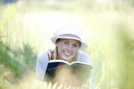 Photo for Smiling woman laying in grass and reading book - Royalty Free Image