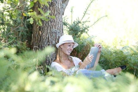 Woman reading novel on tablet