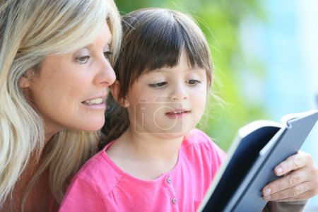 Woman with daughter teaching how to read