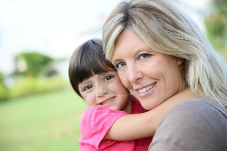 Photo for Cheerful woman embracing little girl in arms - Royalty Free Image