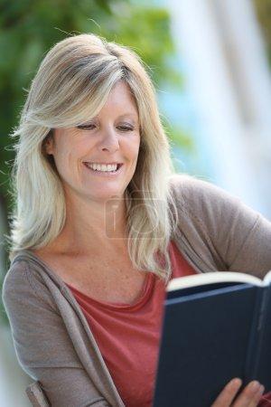 Woman reading book in backyard