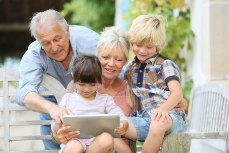 Grandparents playing on tablet with kids