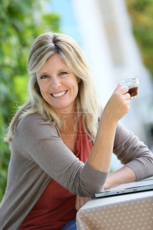 Woman relaxing with tablet in garden