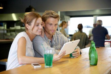 Friends in bar websurfing on tablet