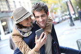 Cheerful couple playing with smartphone