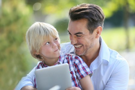 Man with son using digital tablet