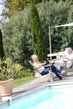 Photo pour Couple de personnes âgées dans l'arrière-cour de lecture réserve en transats - image libre de droit