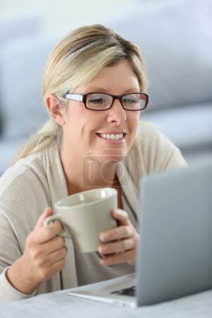 Woman with eyeglasses websurfing on laptop