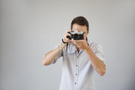 Photo pour Photographe sur fond gris avec appareil photo vintage - image libre de droit