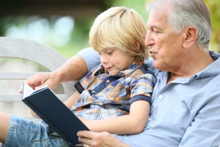 Grandfather reading book with grandson