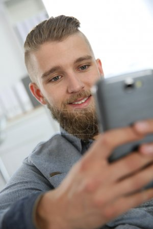 Man sending text message with smartphone