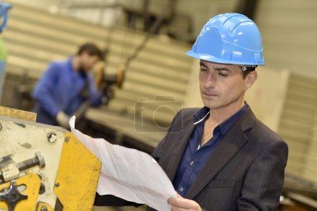 Engineer in factory reading blueprint