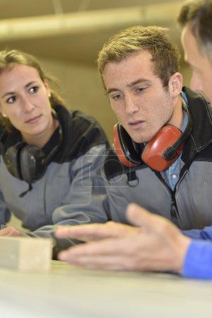 Photo pour Étudiants en menuiserie à l'écoute attentive du formateur - image libre de droit