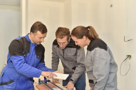 Teacher with students using saw