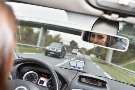 Woman looking at rear view mirror