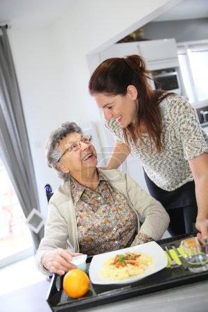 Altenpflegerin bereitet Mittagessen für Frau zu