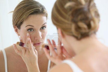 Woman applying concealer around eyes