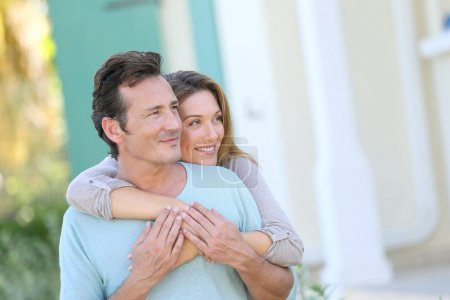 Photo for Middle-aged couple embracing in front of house - Royalty Free Image