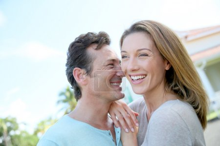 Cute smiling loving couple standing in front of ho...