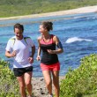 Couple running by sea on track...