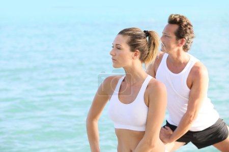 Photo pour Couple doing yoga and relaxation exercises by sea - image libre de droit