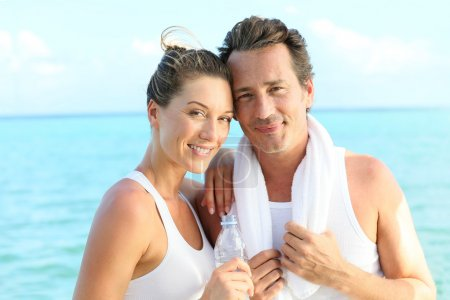 Photo pour Portrait of couple looking at camera after exercising, bottle of water in hand - image libre de droit