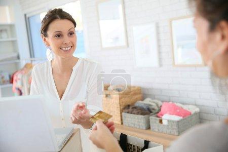 Photo pour Client dans un magasin de vêtements donnant carte de crédit au vendeur - image libre de droit
