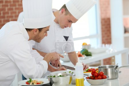 Chef training student in kitchen