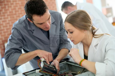Teacher with student repairing computer