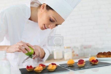 Photo pour Pâtissier râper le zeste de citron sur le gâteau au chocolat - image libre de droit