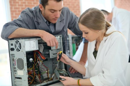 Photo for Teacher with student repairing computer in classroom - Royalty Free Image