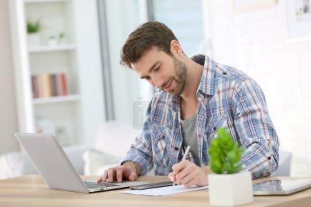 Photo pour Beau homme d'affaires mature à la maison travaillant sur ordinateur portable - image libre de droit