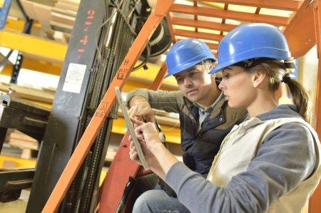 Photo pour Exploitant avec surveillant travaillant en entrepôt - image libre de droit