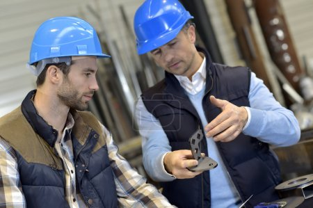 Engineer with worker checking on production