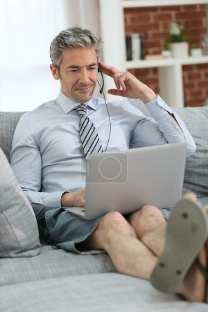 Businessman with headset on couch